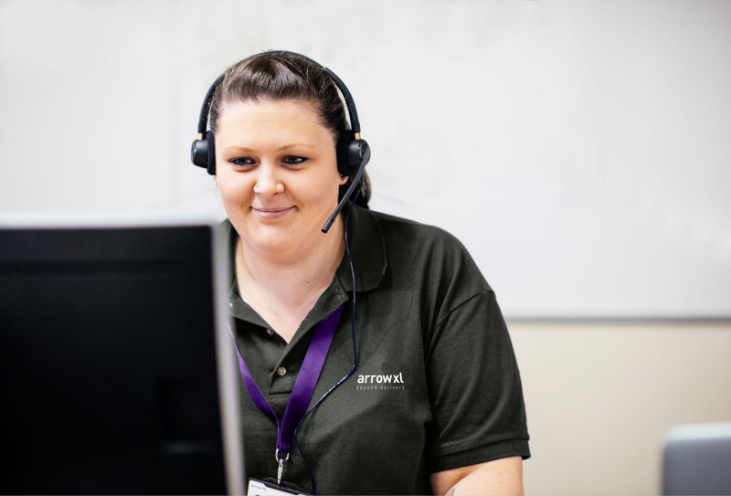 Photograph of an ArrowXL Customer Experience Agent at her desk wearing a headset