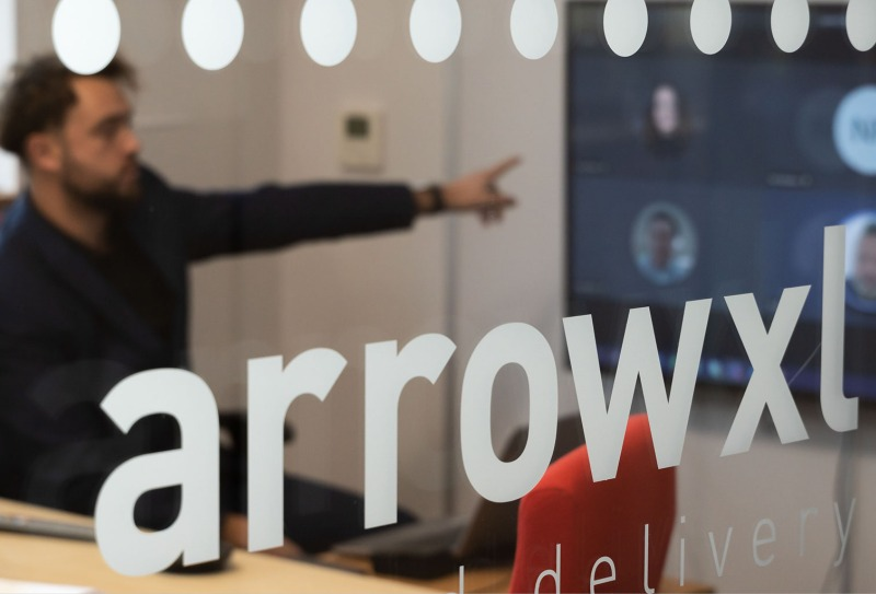 An ArrowXL colleague pointing at a TV meeting with the front of the image showing the ArrowXL logo etched on the meeting room glass